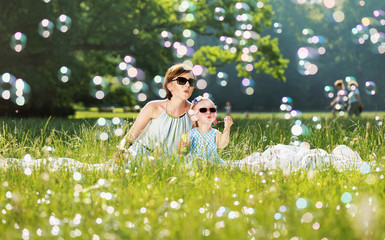 Mother and daughter family time, blowing soap-bubbles