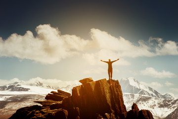 Man in winner pose with raised hands stands on the top of mountains. Win concept