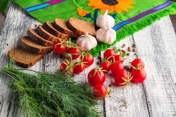 Stilllife on wooden background: tomatoes, black bread, garlic, f
