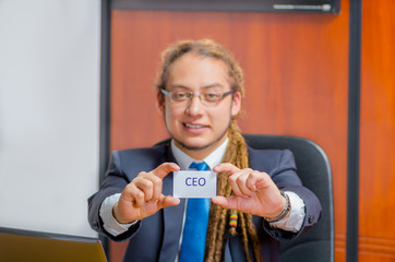 Handsome man with dreads, glasses and business suit sitting by desk holding up a paper which has the word executive written on it in his pocket, young manager concept