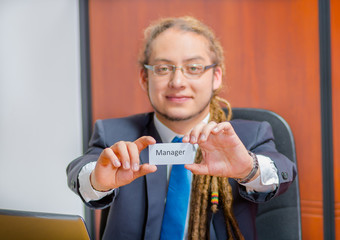 Handsome man with dreads, glasses and business suit sitting by desk holding up a paper which has the word manager written on it in his pocket, young executive concept