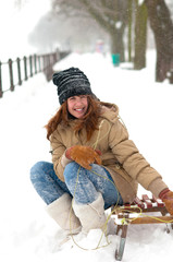 Happy teenage girl sitting on sledges in winter falling snow