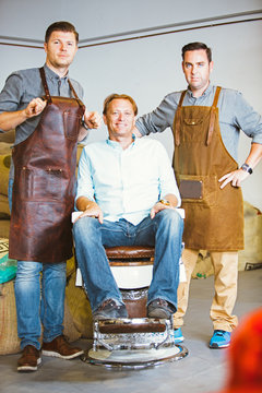 Two workers in aprons with coffee master on chair