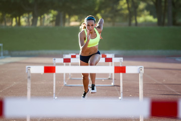 Young athlete jumping over a hurdle during training on race trac