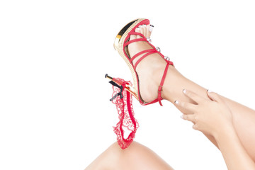 Woman putting off her red garter, playing with it and her shoe. Over a white background, isolated.