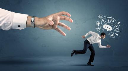 Business man running from a big hand