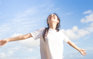 Happy relaxed asian woman breathing deep fresh air and raising arms on the beach with blue sky background