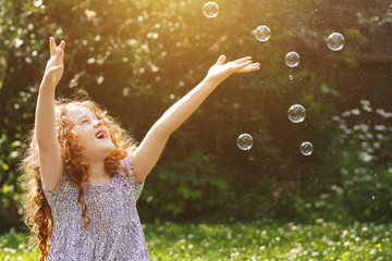 Curly girl catches a soap bubbles. Happy childhood concept.