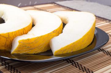 Three slices of juicy yellow melon