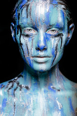abstract art makeup. Face, neck and hair girls smeared with bright colors of blue, blue and silver colors. The paint flows. On the face of silver tears. Holi festival