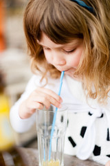 Little girl drinking juice through a straw