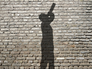 Alcoholism - shadow of a man drinking straight from the bottle in the street