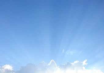 Blue sky with clouds and light shining through.