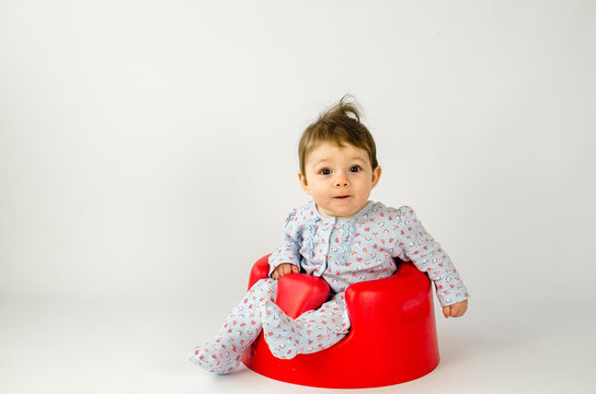cute baby girl sitting in a plastic seat