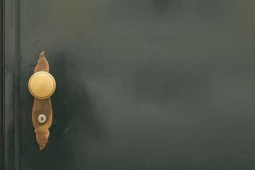 Eine dunkelgrüne Holztür mit goldenem Türknauf.