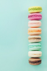 Cake macaron or macaroon on blue background from above. Colorful almond biscuits. Vintage card. Flat lay.
