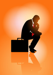 Pensive businessman sitting on his briefcase