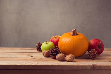 Autumn still life with pumpkin, apples and pine corn on wooden table