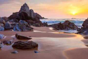 landscape of big rocks the ocean beach at sundown