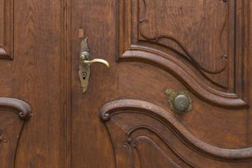 Dunkelbraune Holztür mit wunderschönen, geschwungenen Schnitzereien, Klinke und Knauf