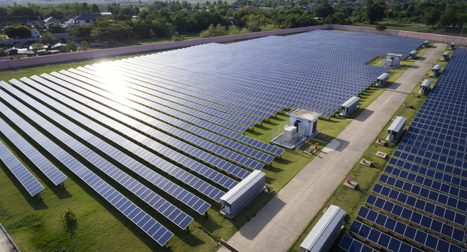 Aerial view of solar farm under sunlight raying on panels