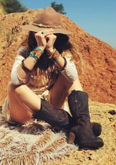 Traveller fashion woman sitting on a fur on rock, safari travel concept
