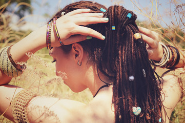 Beautiful young woman wearing dreadlocks hairstyle gathered in a ponytail and decorated assorted beads