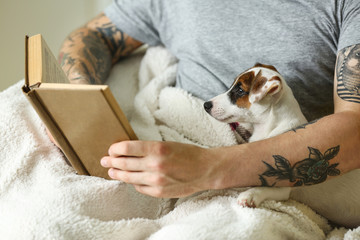 Man with cute dog reading book