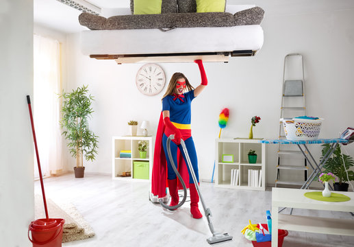 Strong super housewife cleaning home and holding bad in the air
