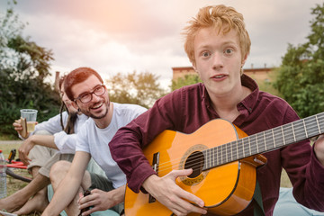 Young red haired boy playing guitar with friends in park