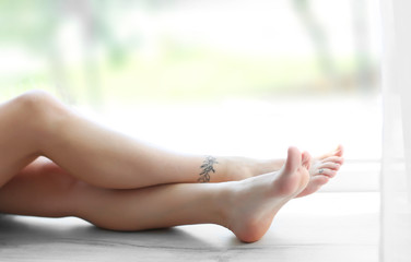 Female legs with tattoos on windowsill