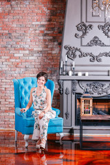 Beautiful woman with blue eyes and curly hair in dress on luxory interer background the fireplace chandelier. sofa