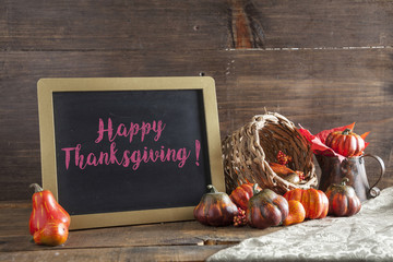 Happy Thanksgiving Written In Red Chalk On Black Chalkboard Background On Aged Wood Table With Thanksgiving Decorations In Selective Focus.