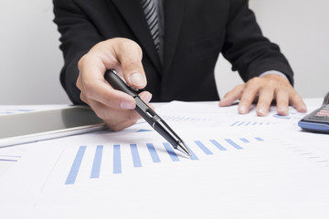 Business man hand pointing at business document during discussion at meeting