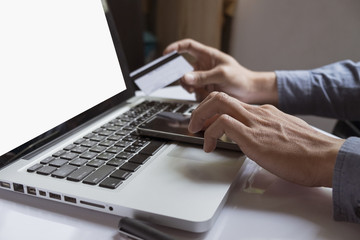 man's hands holding credit card and using laptop. Online shopping