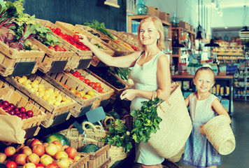 Glad mother with daughter shopping various veggies