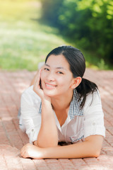 Young asian woman relaxing outdoors looking happy and smiling