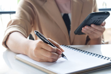 Business girl Hand write note and holding smartphone.