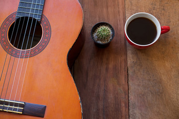 coffee cup and guitar on wooden table