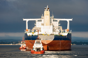 Tugboats towing a large tanker ship in port.