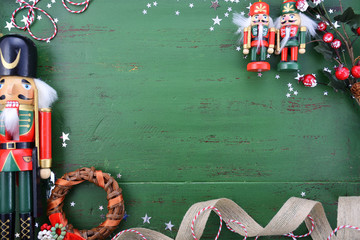 Christmas background with ornaments on green wood table.