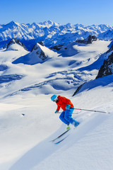 Wall Mural - Male skier skiing in fresh snow off ski slope on a sunny winter day at high mountain in French Alps. Freeski in powder snow.