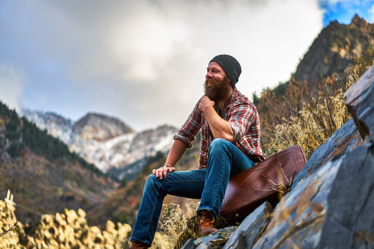 happy bearded guy sitting on luggage at top of mountain