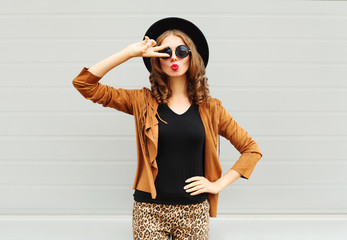 Fashion pretty woman wearing a black hat, sunglasses and jacket