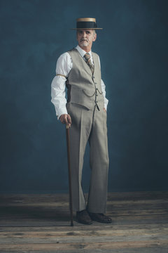 Retro 1920s dandy in suit standing with cane in front of gray wa