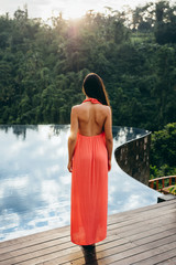 Rear view of woman standing by swimming pool at tropical resort