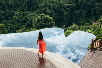 Rear view of woman walking on poolside in tropical resort