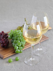 Glasses of wine with grapes on wooden board