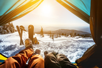 Couple of snowboarder and skier in tent
