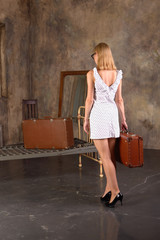Young lonely woman with a suitcase enters the old apartment
